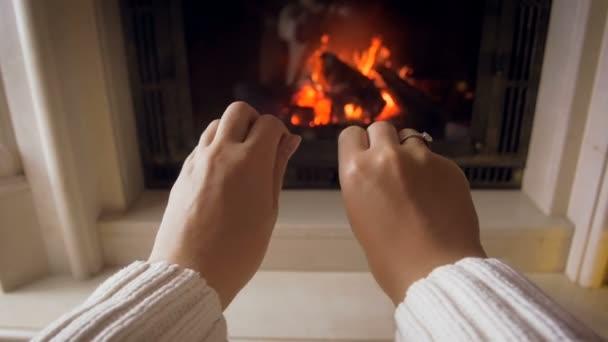 Zeitlupenaufnahmen einer jungen Frau, die ihre kalten Hände auf das brennende Feuer im Kamin ihres Hauses reibt und ausstreckt
