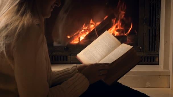 Lassú mozgás video-ból fiatal nő olvasó a könyvet, és lapozható a fényt az égő firepalce