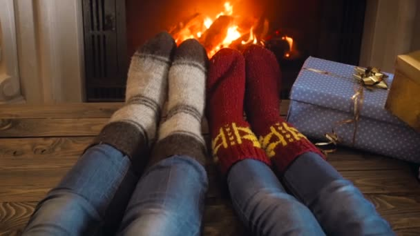 Slow motion video of couple in woolen socks having romantic night at burning fireplace on Christmas eve