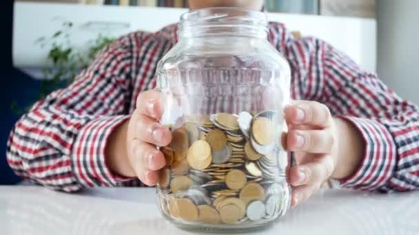 4 k záběry mladého muže, šetří peníze a házení mincí v jar Pokladnička označen úvěr