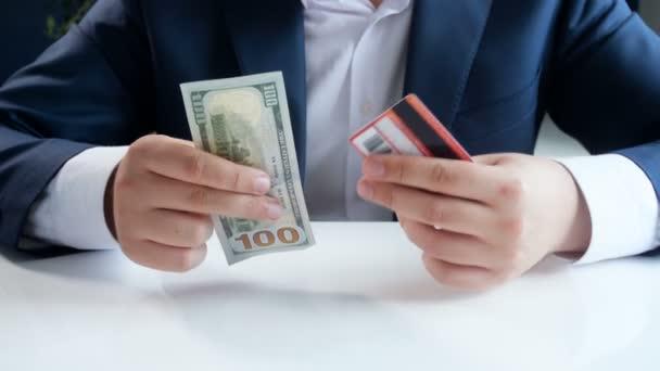 4 k felvételek kiválasztása, hitelkártya helyett papír dollárost fiatal üzletember. A modern technológia, a pénzügyek fogalmát