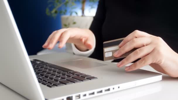 Vértes 4k felvétel, fiatal üzletasszony dolgozik laptop, és a kezében tartja a hitelkártya