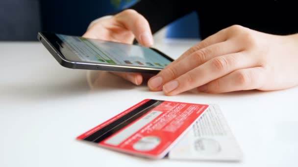 Closeup footage of young woman browsing online stores on smartphone. Two credit cards lying on table next to her.