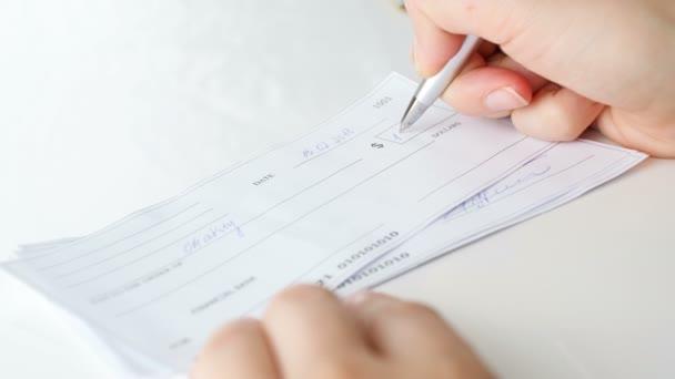 Nahaufnahme 4k Filmmaterial von junger Frau beim Unterschreiben eines 1000-Dollar-Schecks mit Stift