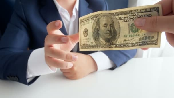 Closeup 4k footage of person giving 100 US dollar to bribed politician or official at office