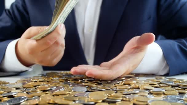 Slow motion video of successful businessman sitting at desk full of money and playing big stack of US dollars