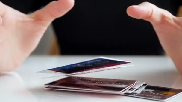 Zeitlupenvideo einer jungen Geschäftsfrau, die einen großen Stapel Bak-Kreditkarten vor sich auf den Schreibtisch wirft