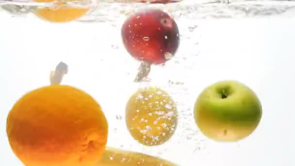 Closeup 4k footage of bananas, apples, oranges, lemons and grapefruits falling in water against white background. Fresh juicy fruits underwater