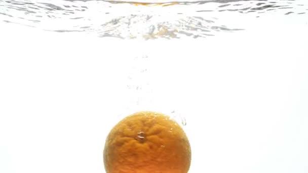 Detailní video Orange pomalu klesá a šplouchání v jasné chladné vodě proti bílým pozadím