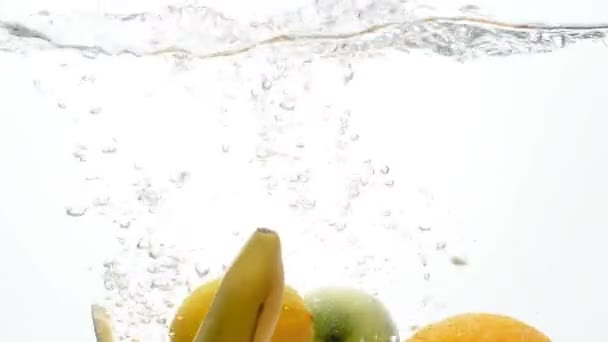 Closeup slow motion video of fresh and ripe tropical fruits falling and splashing in water against white background