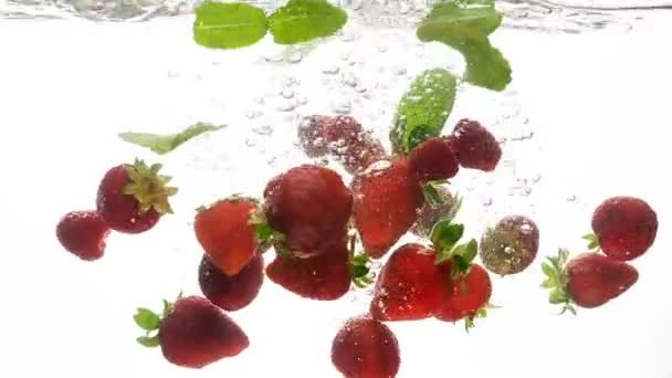 Closeup slow motion video of fresh ripe strawberries and green mint leaves falling and splashing in cold clear water. Concept of freshness