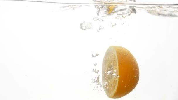 Detailní zpomalené záběry z tropických citrusových plodů půlky pádu a postříkání čistou studenou vodou