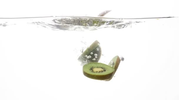 Closeup slow motion video of cut ripe kiwi fruit falling in clear cold water against white background