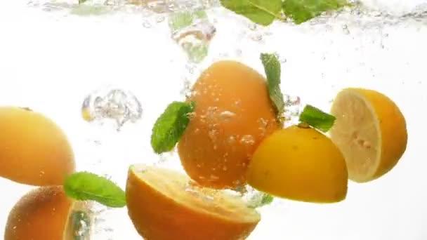 Detailní zpomalené záběry šťavnaté a zralé citrusových plodů pádu do vody. Poloviny pomeranče a citrony s mátou listí, šplouchání ve vodě