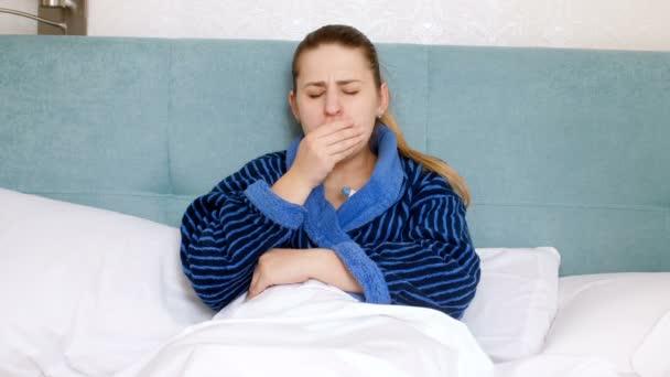 4k Filmmaterial einer jungen, grippekranken Frau, die im Bett liegt und die Temperatur misst