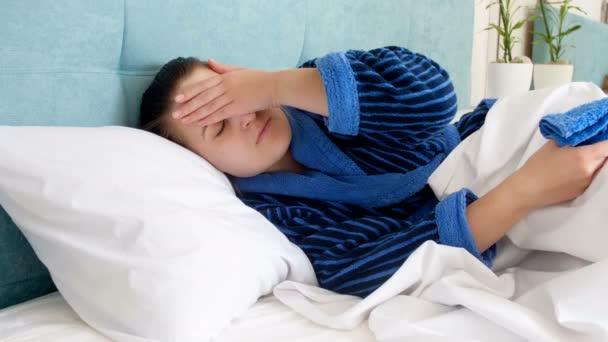4 k záběry z mladých nemocná žena v županu, ležící v posteli, dotýká její čelo a uvedení mokrý studený ručník na hlavu