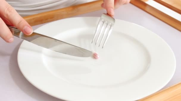 Conceptual 4k video of woman on diet eating small pills for loosing weight with fork and knife