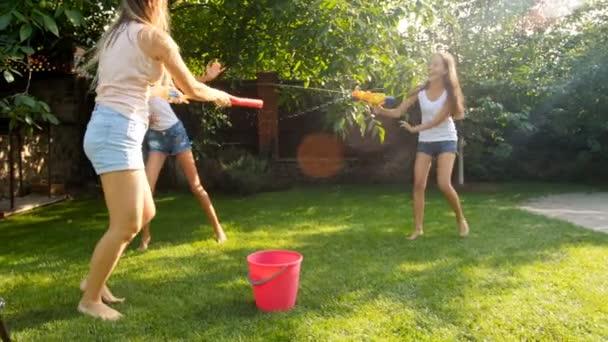 4 k Aufnahmen von zwei lachende Mädchen mit jungen Mutter Spritzwasser mit Spielzeugpistolen im Hinterhof