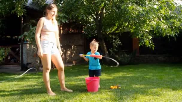 4k video des kleinen Kleinkind jungen Füllung Spielzeugpistole mit Wasser und spritzt in zwei ältere Schwester an heißen sonnigen Tag