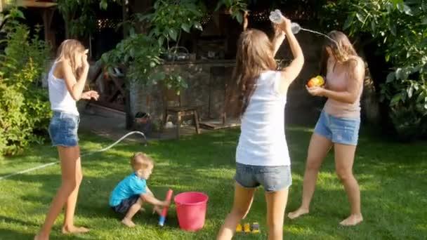 4 k Video von der glückliche junge Familie Planschen und gießt Wasser über einander an heißen, sonnigen Tag auf dem Rasen im Garten