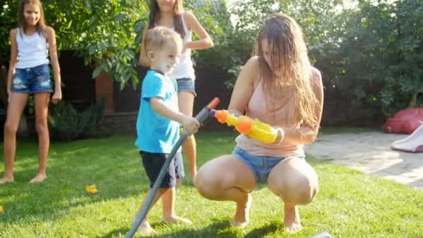 4k Filmmaterial von niedlichen lachenden Kleinkindern, die mit Gartenschlauch auf dem Rasen im Hinterhof spielen