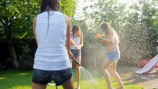 Slow-Motion-Video von Mutter und zwei Mädchen spielen mit Wasserpistolen auf dem Rasen im Garten