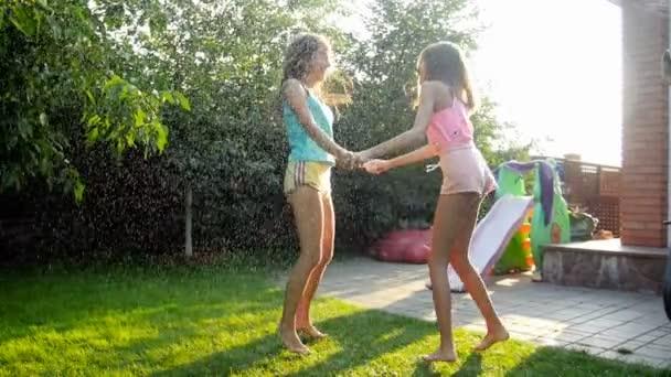 Zeitlupenaufnahmen von zwei fröhlich lachenden Mädchen, die Händchen halten und auf dem Gras im Hinterhof unter spritzendem Wasser aus dem Gartenschlauch tanzen
