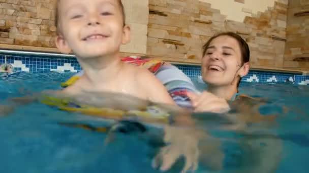 4 k video s úsměvem 3 roky starý chlapeček s nafukovací barevný kroužek plavání v krytém bazénu