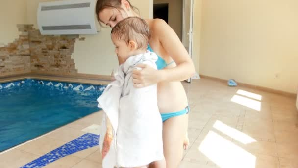 4k video of young caring mother wiping with towel her wet little son after swimming at pool