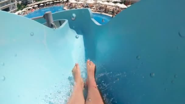 Slow motion POV video of young man riding down on water slide at aquapark
