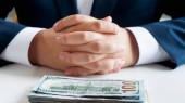 Closeup image of businessman sitting behind office desk with big stack of money