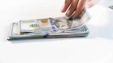 Closeup photo of hand grabbing 100 dollars from big stack of money on white backgorund