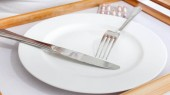 Closeup image of fork and knife lying on empty white plate. Concept of diet and loosing weight