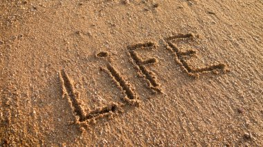 Closeup image of word Life written on wet sand at beach