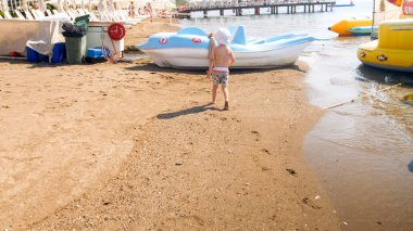 Rera view image of little toddler boy walking on sea beach toward boats and catamarans