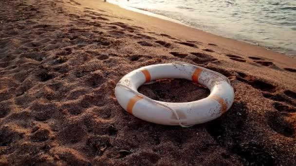 4k Filmmaterial vom Rettungsring, der bei Sonnenuntergang am Strand liegt