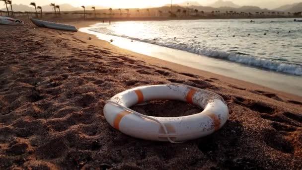 4k Filmmaterial vom Rettungsring, der bei Sonnenuntergang am Sandstrand liegt
