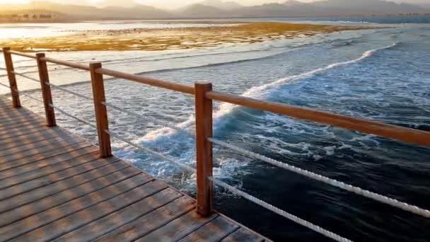 4k video dlouhého dřevěného mola v oceánu. Mořské vlny převalované přes pobřeží