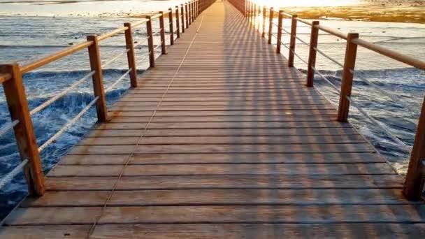 4k video o procházce po nekonečné dřevěné molu v oceánu. Velké vlny se valnou přes pobřeží