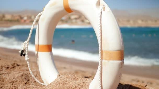 4k Zeitlupe Video von Rettungsring Boje am Sandstrand bei windigem Tag am Strand