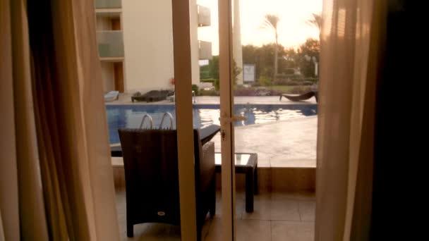 4k Zeitlupenvideo vom Verlassen der luxuriösen Villa und dem Blick auf den Swimmingpool bei Sonnenuntergang