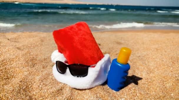 4k záběry Santa klobouku ležící na písečné pláži. Koncept oslavy vánočních svátků na tropických ostrovech