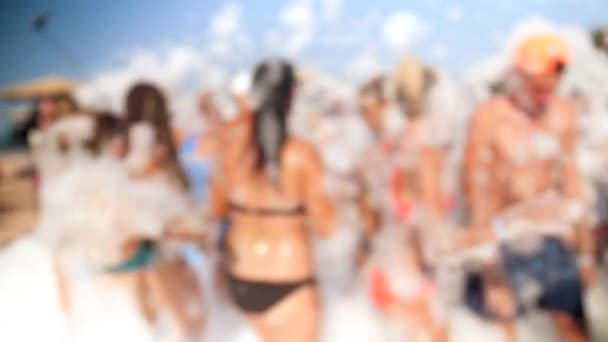 4k video of cheerful crowd in swimsuits and bikinis dancing on the beach at bright sunny day. Young people having soap foam party
