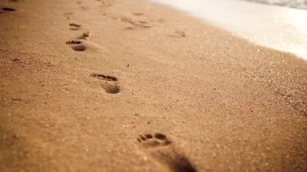 4k Footage lábnyomok a Golden Beach homokkal naplementekor fény