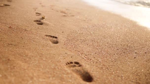4k Vértes videó az emberi lábnyomok a nedves homok mellett gördülő tengeri hullámok