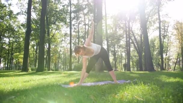 4k pomalý film s usměvavou ženou, která cvičila jóju a medituje v parku za slunného letního dne