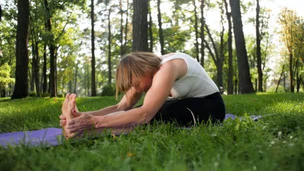 4k záběry šťastné usměvavé ženy, která se táhne na fitness rohože v parku. Dáma středního věku dělá v lese cvičení jóby.