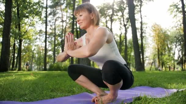 4k Zeitlupenaufnahmen einer lächelnden Frau mittleren Alters, die an einem sonnigen Sommertag im öffentlichen Park Yoga praktiziert. Konzept der körperlichen und geistigen Gesundheit