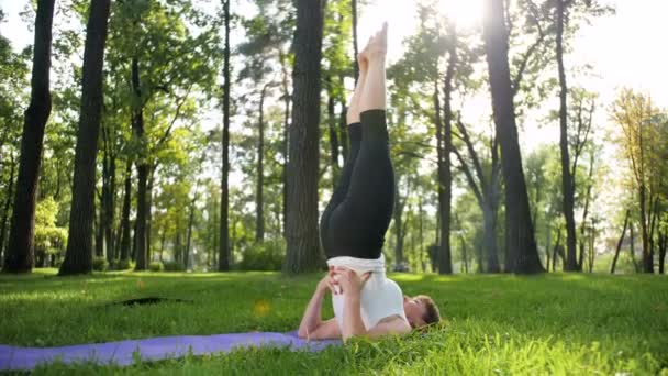 4k slow motion video of yoga and fitness on grass at park. Middle aged smiling woman practicing and doing exercises on sunny day at forest. Female taking care of her mental and physical health