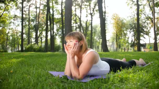 4k pomalý pohyb s usměvavou ženou, která ve slunném letním dnu trénuje jóju ve veřejném parku. Koncepce tělesného a duševního zdraví